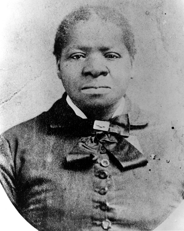 Black and white portrait of Biddy with buttoned dress and ribbon around neck. Her hair is pulled back.