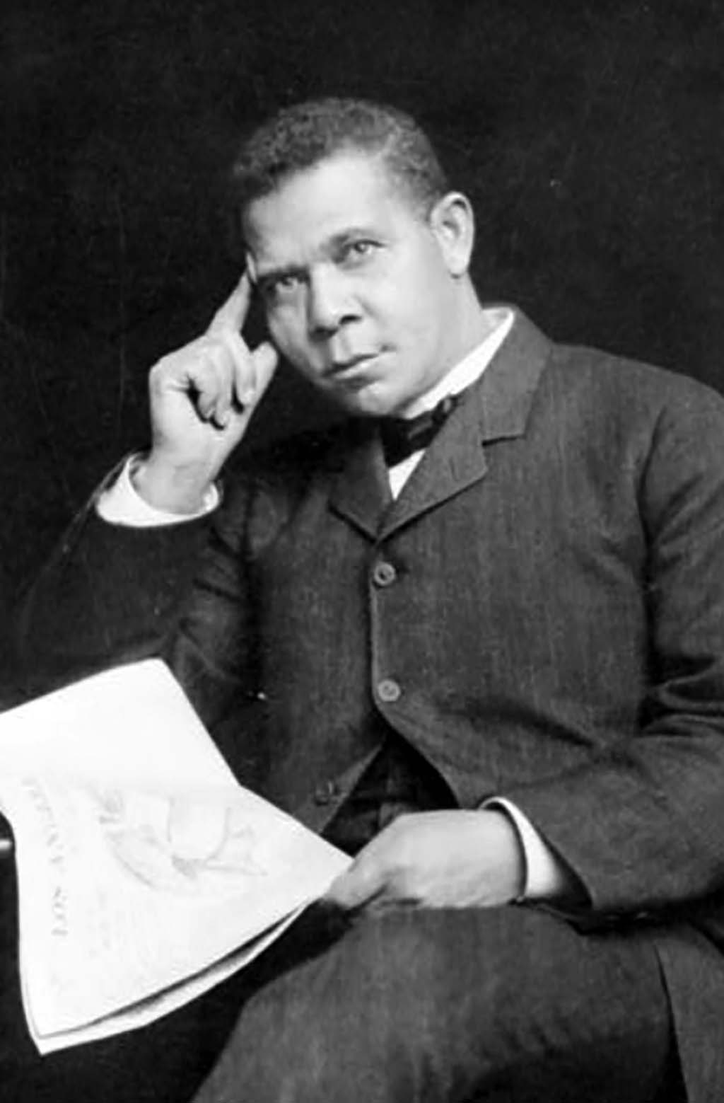 Booker T. Washington, three-quarter length portrait, seated, facing slightly left, holding newspaper