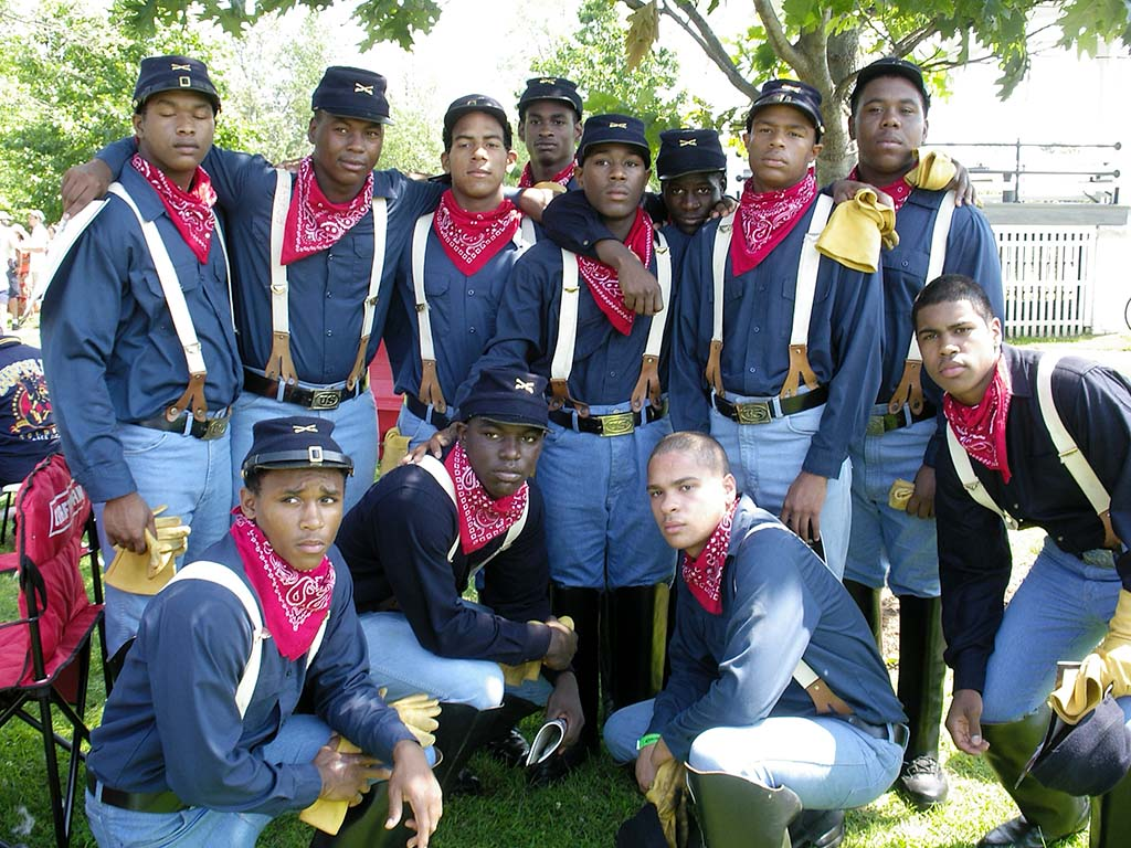 12 young men with blue shirts, blue jeans, blue caps, white suspenders, yellow gloves, and red bandanas around necks