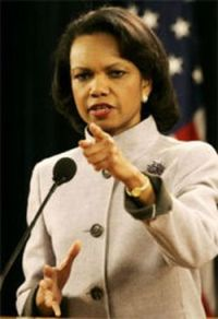 Condoleeza Rice standing at a microphone pointing towards the audience