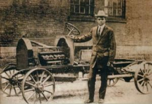C.R. Patterson standing in front of early model car