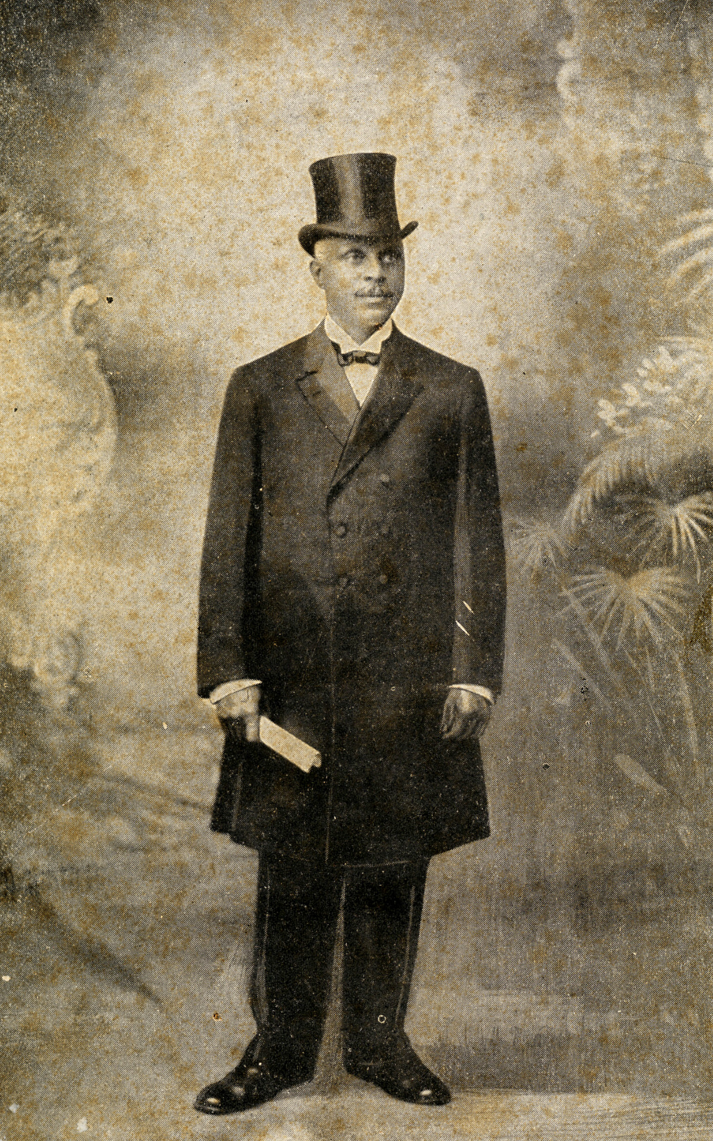 Taylor wearing a dark suit and top hat and holding what looks like a folded paper.