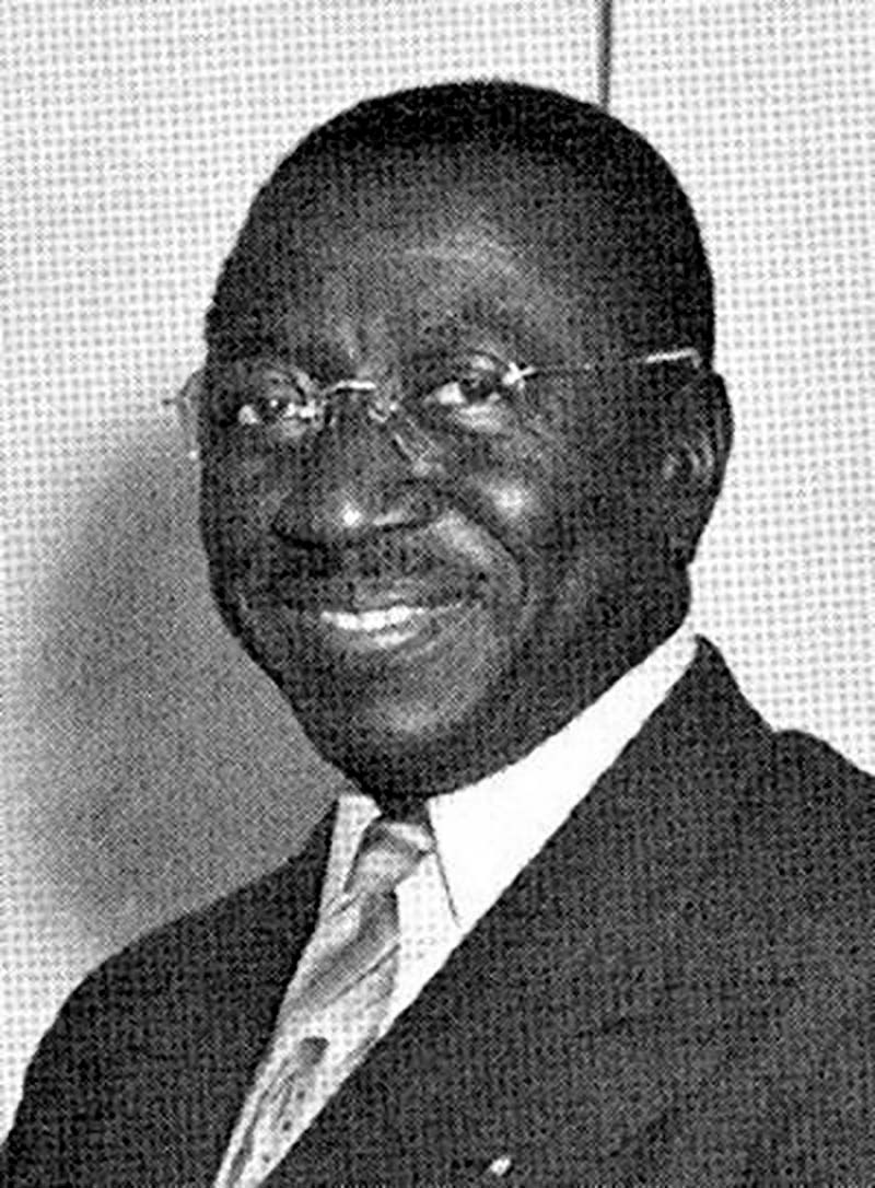Black and white school employee portrait. Man wearing glasses with suit and tie.
