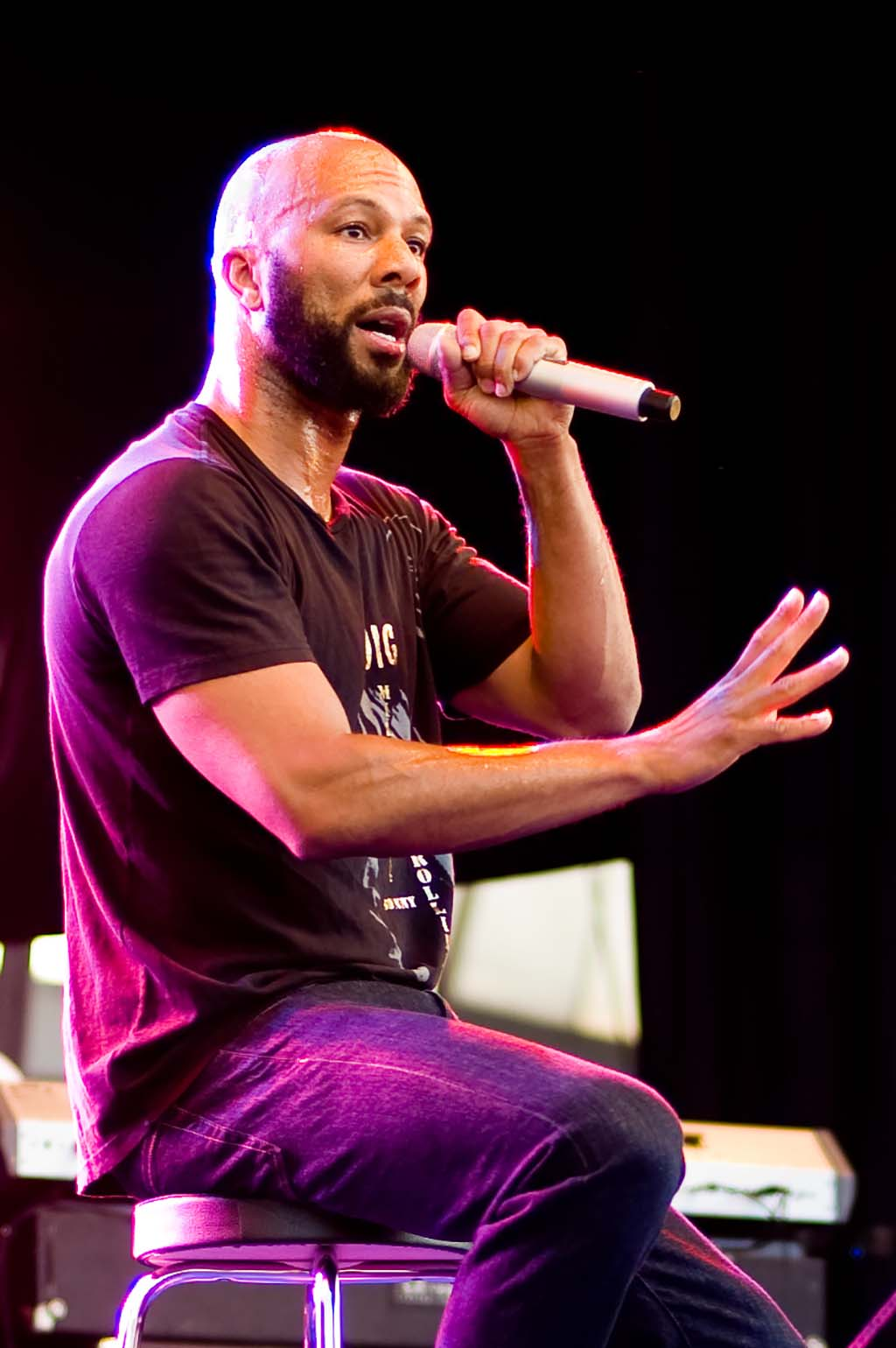 Man with beard talking in microphone while sitting on stool. Motioning with his hand. Purple backlighting.