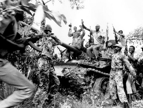 Second Sudanese Civil War (Guerrilla forces of the Sudan People's Liberatio Army celebrate over a disabled tank