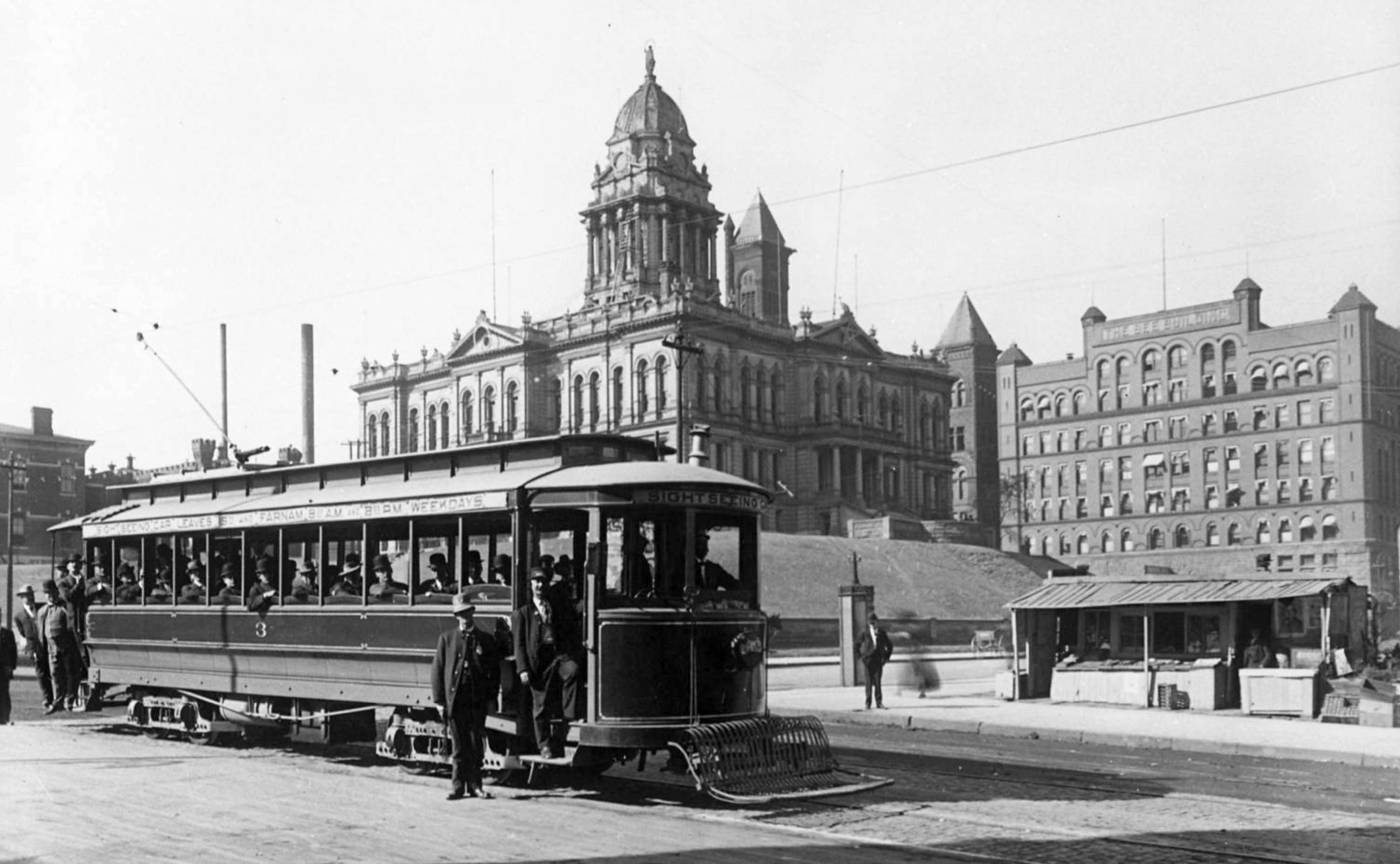 Black and white street-view of a streetcar in the foreground, overflowing with people posing for the photo. Center-background is the Douglas County Courthouse.