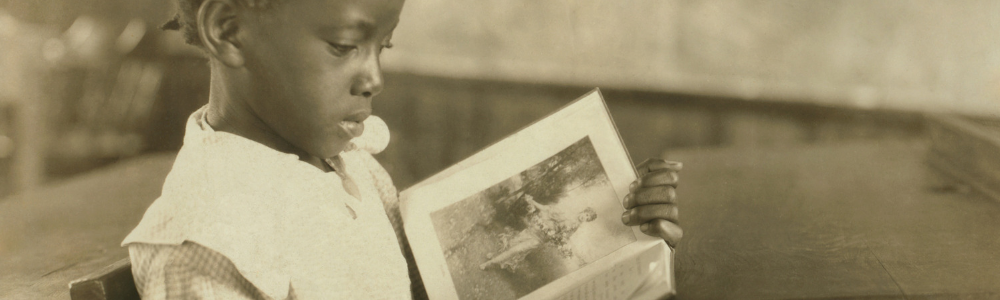 young black girl reading a book