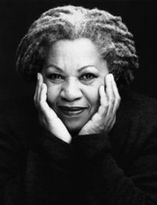Black and white photo of Toni Morrison cradling her chin with her hands and smiling at the camera