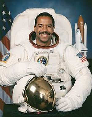 Harris posing wearing a space suite in front of a shuttle model and an American flag. His helmet is off, showing his mustached smile.