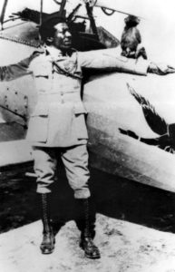 Black and white photo of Eugene Jacques Bullard standing in front of a small plane