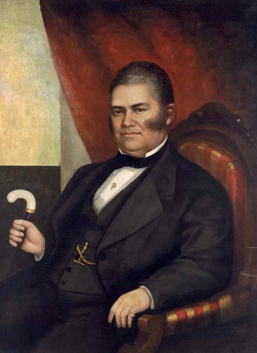 Middle-aged man with soft hooked side burns, wearing a suite. He is holding a cain with a white handle and sitting on a red and yellow cushioned wood chair.