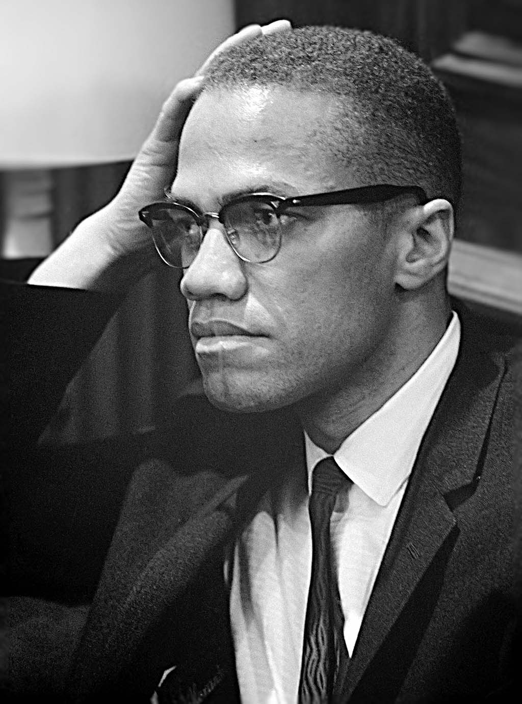 Portrait of Malcolm X at a Martin Luther King Press Conference on March 26, 1964. Malcolm X appears to be listening, with his head resting on his hand.