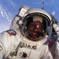 selfie of Winston Scott wearing a space suit with Earth behind him